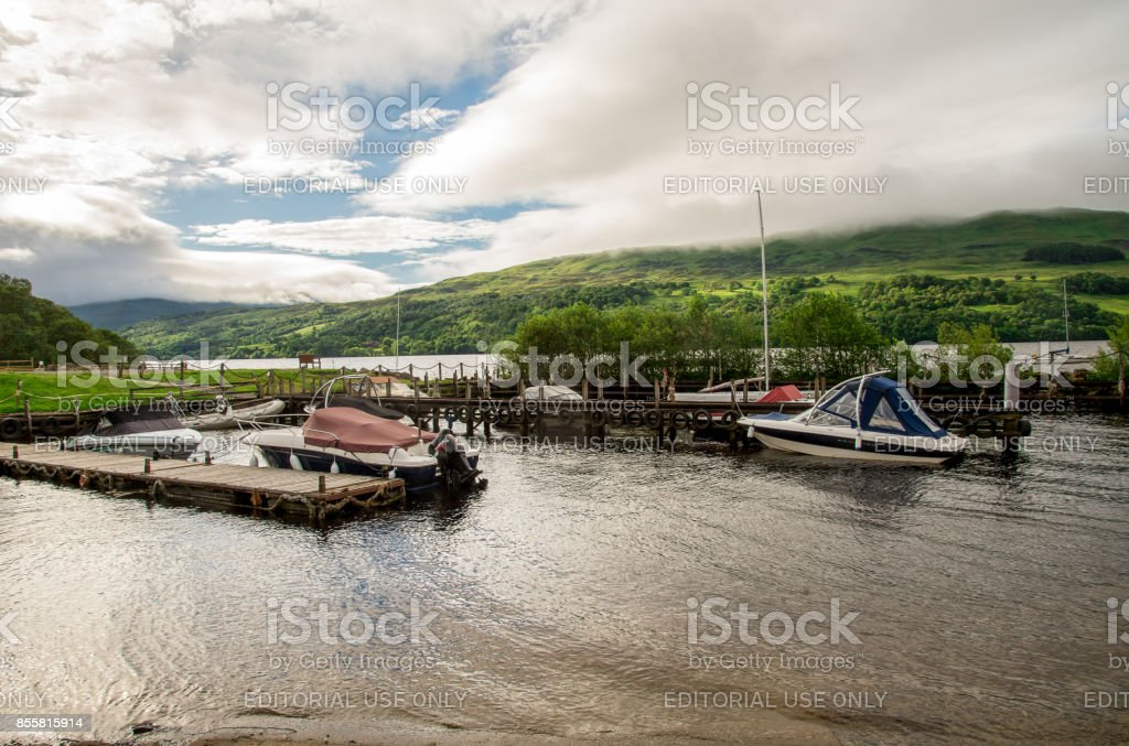 A view of Loch Tay boat station with background highland hills in cloudy weather, central Scotland stock photo