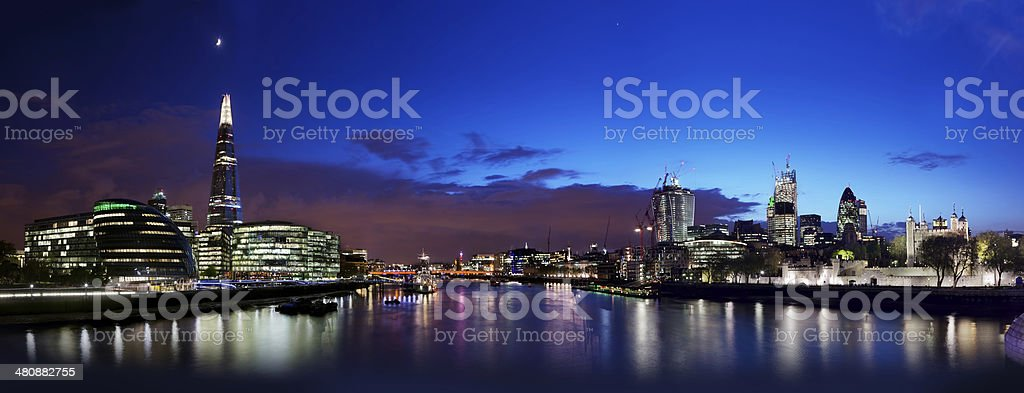 View of London skyline at night from Tower Bridge stock photo
