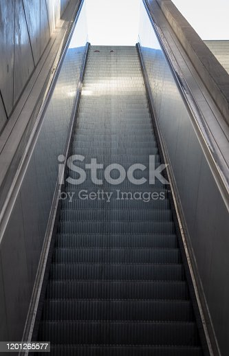 View of long escalators with stainless steel cladding and exposed concrete walls