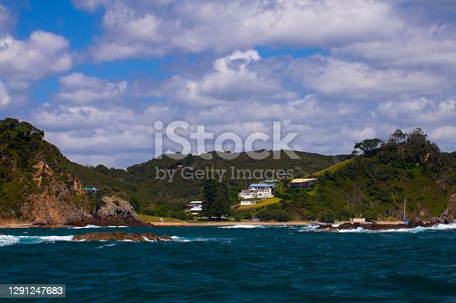 View of lush, rocky coastline at one of over 140 subtropical islands in the Bay of Islands area on the north island of New Zealand