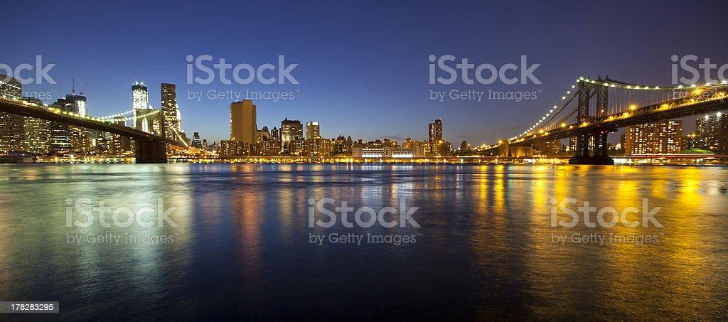 View of Manhattan, Brooklyn bridges and skyline at night stock photo