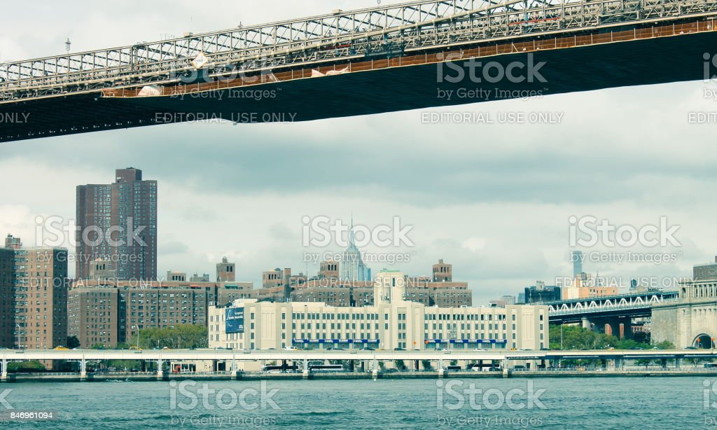 View of Manhattan buildings lining the East River along FDR Drive from beneath the Brooklyn Bridge stock photo