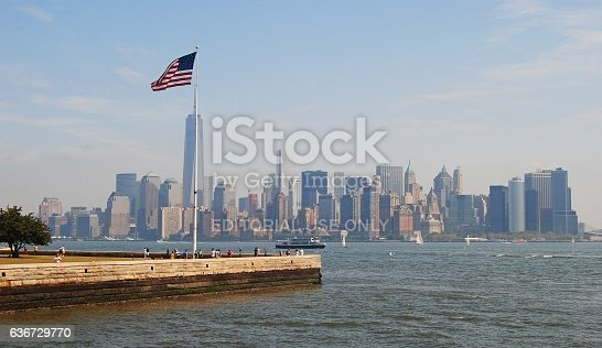 New York, United States of America - September 6, 2014. View of Manhattan from the Ellis Island, with American flag, people and Manhattan skyscrapers in the background.