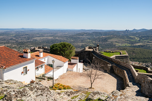 View of Marvao village with beautiful houses and church with rocky landscape mountains behind