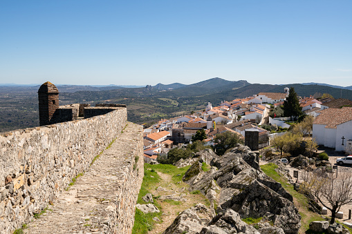 View of Marvao village with beautiful houses, church and wall with rocky landscape mountains behind
