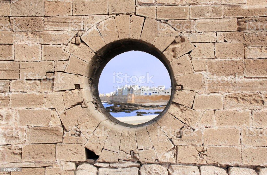 View of medina Essaouira through a hole in wall, Morocco stock photo