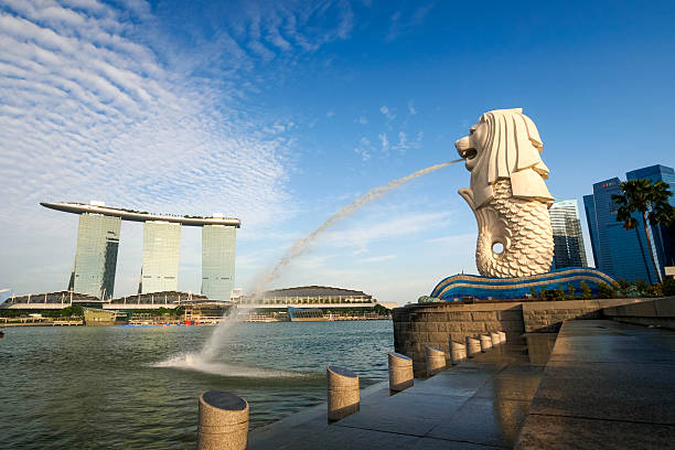 View of Merilon Statue at Marina Bay Singapore City, Singapore - June 20, 2014: View of Merlion Statue at Marina Bay in Singapore with tourists and Singapore Skyline in background. merlion statue stock pictures, royalty-free photos & images