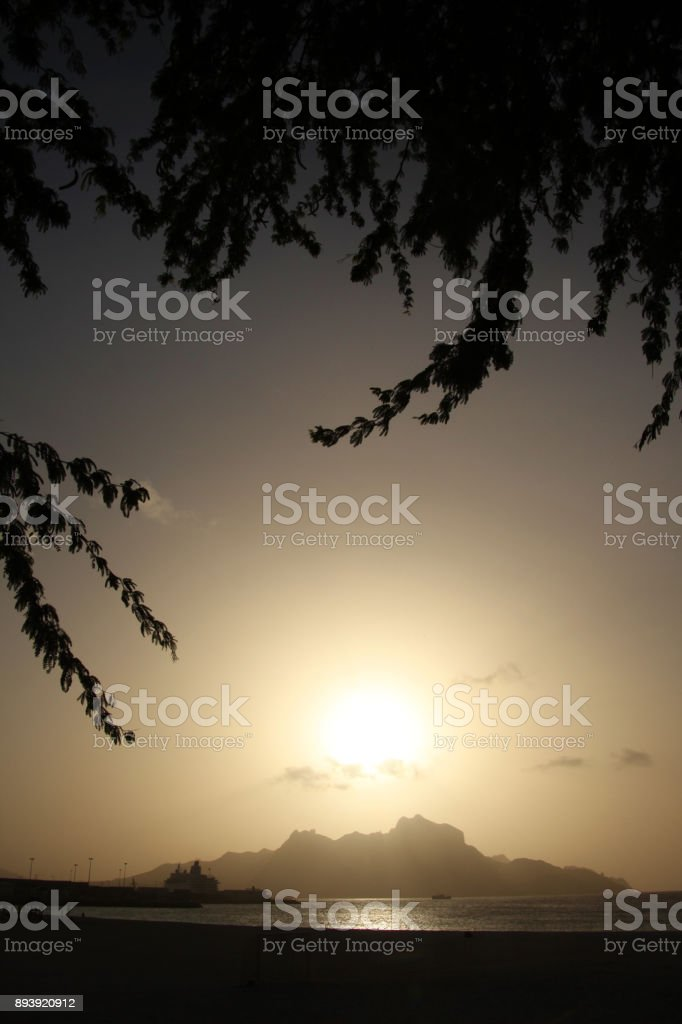 View of Monte Cara mountain from Mindelo framed with tree branches, São Vicente, Cape Verde at sunset. stock photo