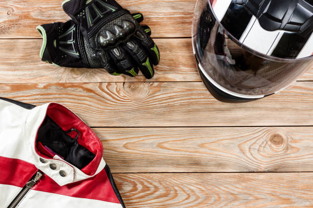 View of motorcycle rider accessories placed on rustic wooden table. stock photo