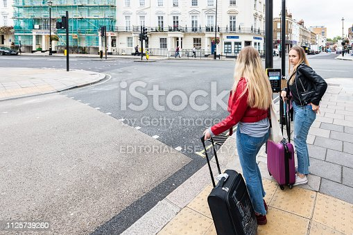 istock View of neighborhood of Pimlico street road with historic architecture and people girls with luggage waiting to cross street 1125739260