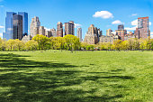 Iconic view of sunlit New York city skyline from flourishing Central Park at spring, with people enjoying the weather during sunny day