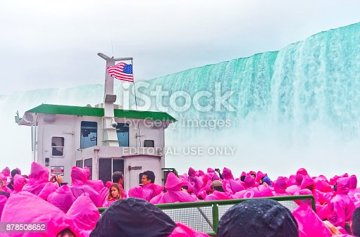 Niagara Falls, USA - October 13, 2013: View of Niagara Falls from the tour boat - Maid of the Mist with lots of tourists wearing purple raincoat on October 13, 2013.