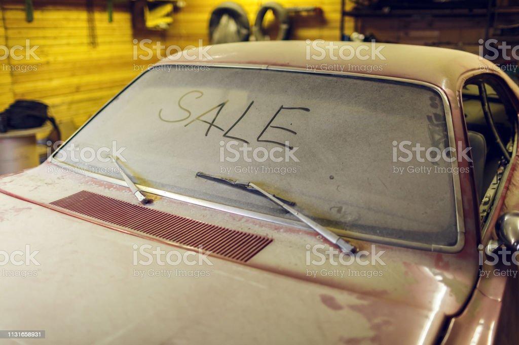 Blick auf altes Auto in der Garage mit staubiger Kapuze schmutzigen Windschutz mit Titel SALE mit dem Finger und gebrochenen Scheibenwischer. Konzept des Verkaufs vorowne Autos. – Foto