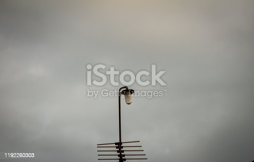 Steel pole with lamp and television antenna with natural overcast sky background