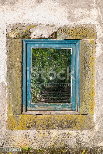 View of old window with frames in blue wood, glass with reflection of a staircase in the forest with tunnel effect, in Portugal