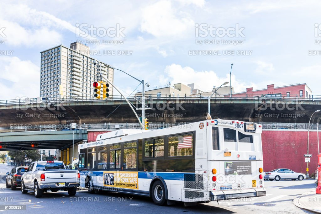 View of outside exterior outdoors in NYC New York City, electric hybrid bus, cars traffic, overpass bridge stock photo