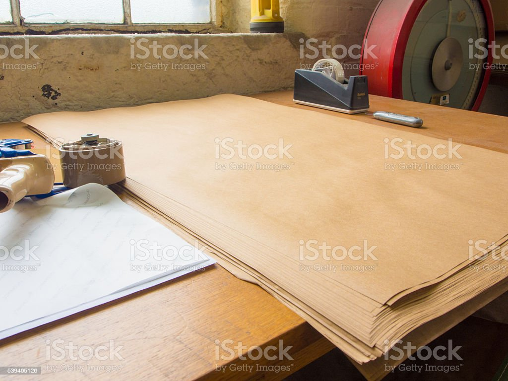 View of Packing & Packaging Table with Brown Paper stock photo