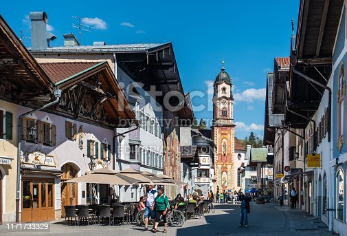 MITTENWALD, GERMANY - View of famous Painted Buildings and Church Tower in the historic Center of Mittenwald in Bavaria with people