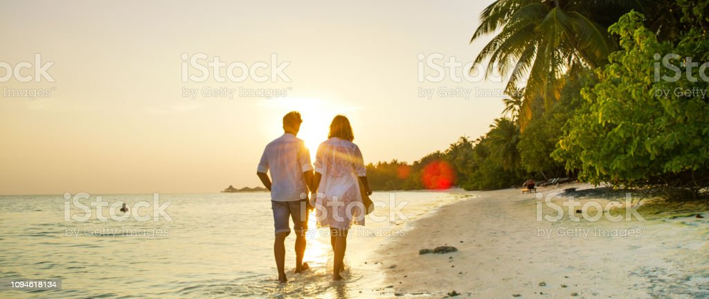 View of pair walking in water,Maldives View of pair walking in water and holding hands,Maldives Adult Stock Photo
