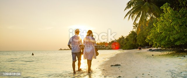 View of pair walking in water and holding hands,Maldives