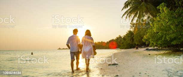 View Of Pair Walking In Watermaldives Stock Photo - Download Image Now