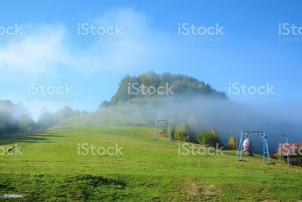 View of Pass Nimchich in sunny autumn morning, blue sky and fog over mountain. stock photo