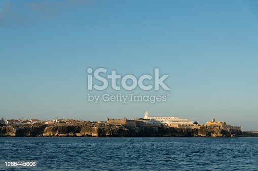 View of Peniche fortress and cliffs of Carvoeiro cape from the sea at sunset, Atlantic coast, Portugal