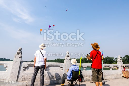Beijing, China - May 25, 2018: View of people and traveler are flying the kites to the sky around the Summer Palace, is a vast ensemble of lakes, gardens, and palaces in Beijing, China.
