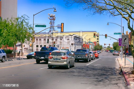 View of people and vehicles in downtown 6th and Broadway in Tucson AZ