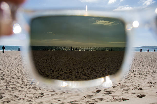 View of people enjoying the beach through sunglasses stock photo