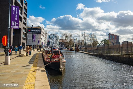 Manchester, United Kingdom - March 1, 2020: View of people walking and boats moored in a canal in New Islington, a newly developed area in Manchester