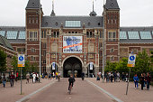 View of people walking and riding bicycles in front of Rijksmuseum. It is a Dutch museum dedicated to arts and history, located at the Museum Square in the borough Amsterdam South.