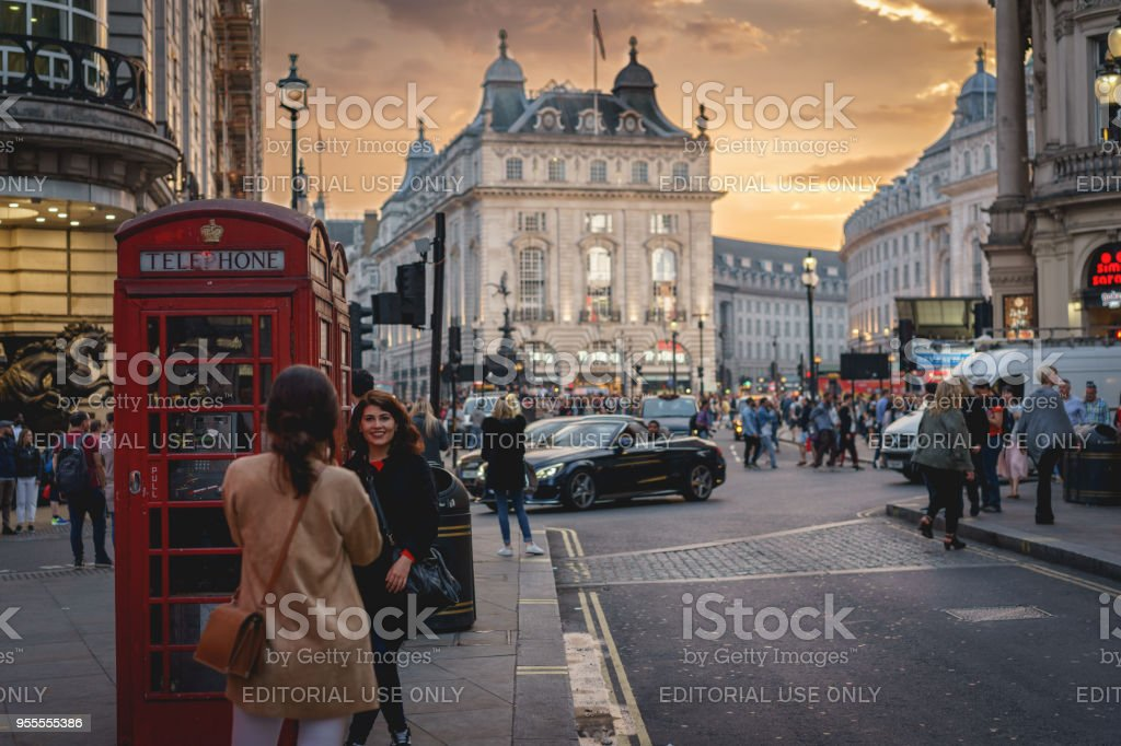 View of Piccadilly Circus in central London crowded with tourists. It is one of the most visited landmarks with its iconic billboards, double-decker buses and taxis. stock photo