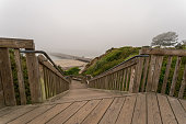 View of Pier With Heavy Fog From Top of Wooden Stairs