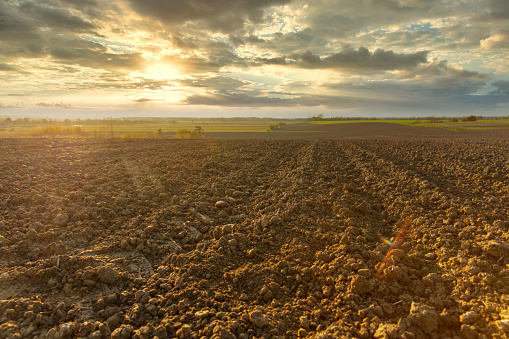 View of plowed field against cloudy sky