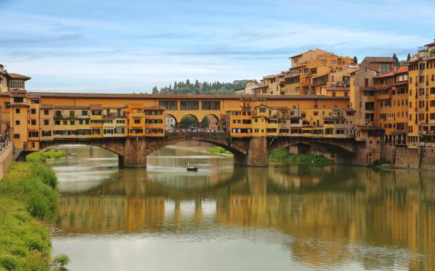 View of Ponte Vecchio bridge across Arno river in Florence (Firenze), Tuscany, Italy stock photo