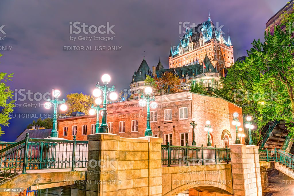 View of Porte Prescott bridge and Chateau Frontenac by old town street Cote de la Montagne with stone buildings at night with lights, lamps stock photo