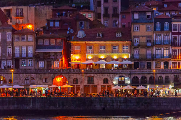 view of porto riverside, people eating and drinking at cafes, taken at night. - esplanada portugal imagens e fotografias de stock