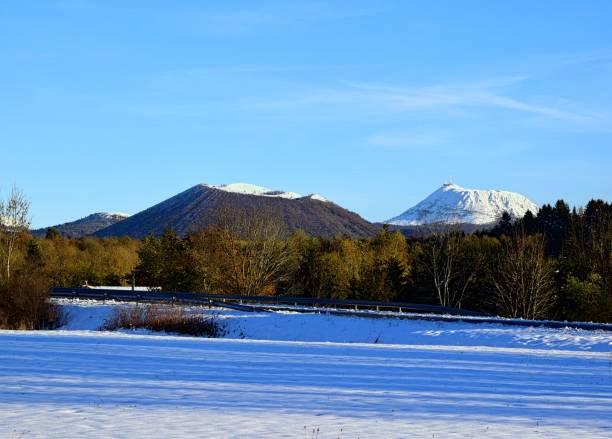 vue des volcans puy de côme et puy de dôme en hiver - chaine des puys photos et images de collection