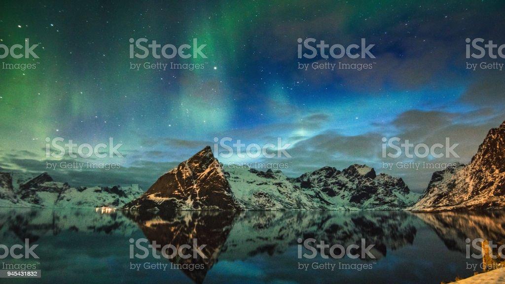 view of reine at lofoten with the aurora borealis stock photo