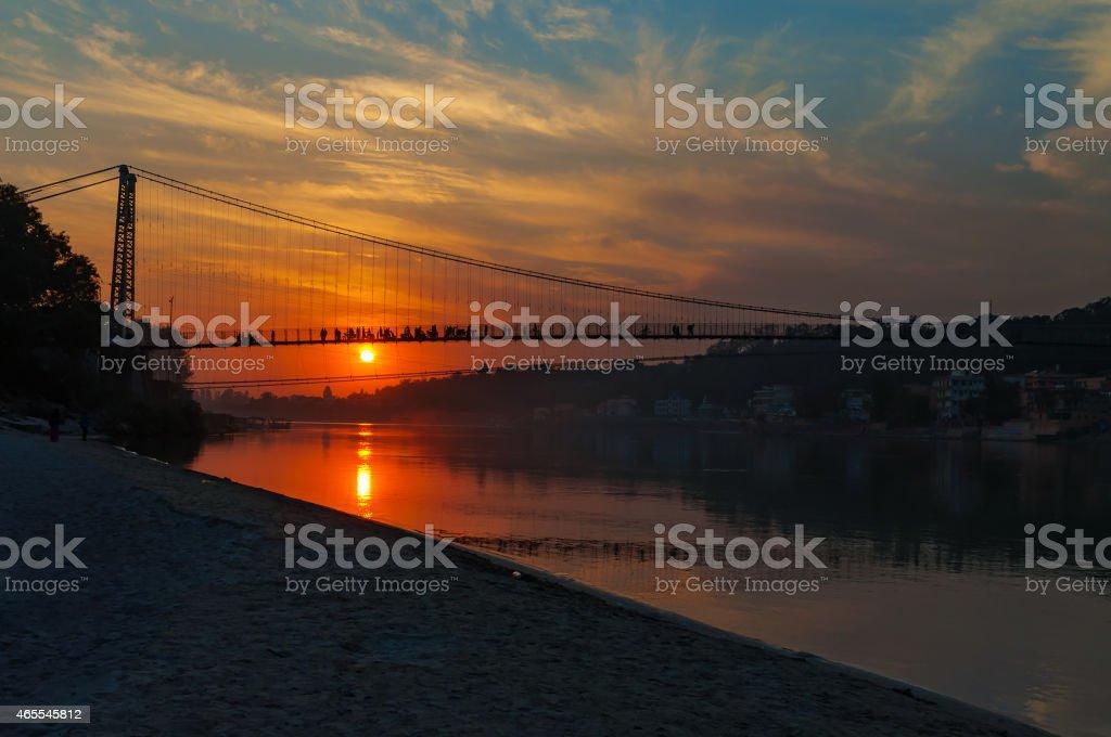 View of River Ganga and Ram Jhula bridge at sunset stock photo
