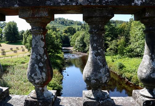 River view through old stone bridge parapet