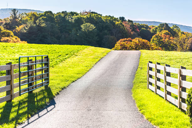 View of road driveway through scenic farm fields land and appalachian mountains in Bath County, Virginia with fence and open gate stock photo