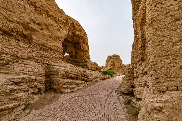 View of Road Through Jiaohe Ruines, Xinjiang, China. Jiaohe or Yarkhoto is a ruined city in the Yarnaz Valley, 10 km west of the city of Turpan in Xinjiang Uyghur Autonomous Region, China. It was the capital of the Jushi Kingdom. It is a natural fortress on the Silk Road located atop a steep cliff between two deep river valleys. silk road stock pictures, royalty-free photos & images