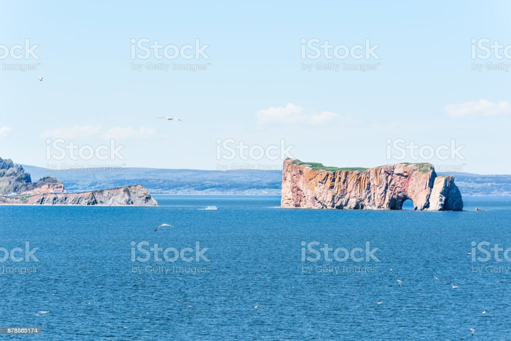 View of Rocher Perce from Bonaventure Island with ocean and gannet birds flying, cityscape skyline or coastline of city stock photo