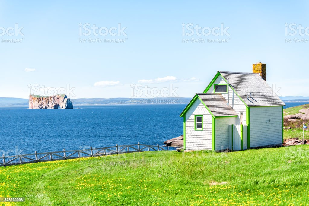 View of Rocher Perce rock and arch from Bonaventure Island with ocean and green wooden painted house, coastline stock photo