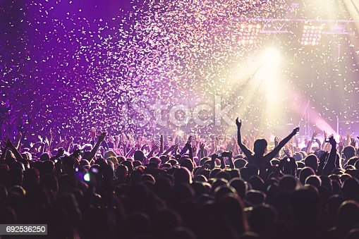 istock View of rock concert show in big concert hall, with crowd and stage lights, a crowded concert hall with scene lights, rock show performance, with people silhouette 692536250