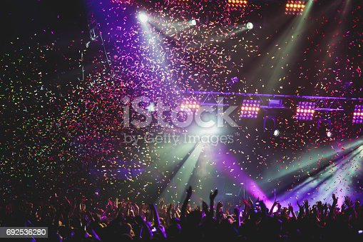 istock View of rock concert show in big concert hall, with crowd and stage lights, a crowded concert hall with scene lights, rock show performance, with people silhouette 692536280