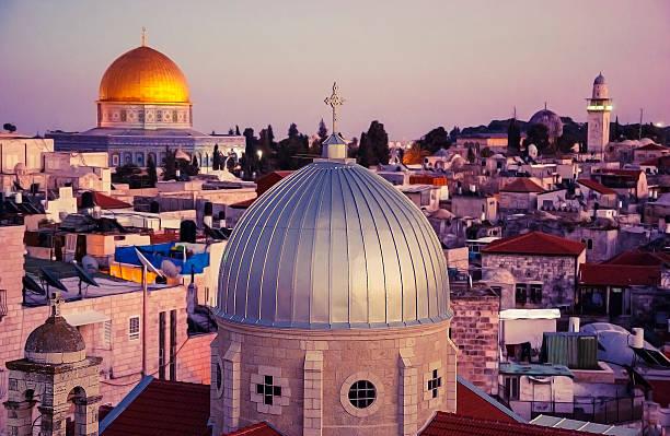 View of rooftops of Old City of Jerusalem at sunset. A view of rooftops of Old City of Jerusalem at sunset. Grey dome of Church of Our Lady of the Spasm (Armenian church) and golden Dome of the Rock. historical palestine stock pictures, royalty-free photos & images