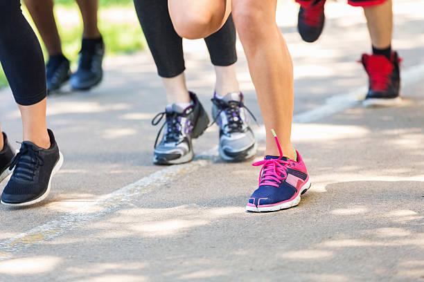 blick auf die läufer füße beim marathon oder 5 km lauf - damenschuhe k stock-fotos und bilder